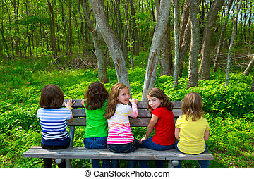 Children sister and friend girls sitting on forest park bench