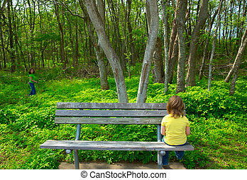 Lonely children sad looking the forest sitting on bench