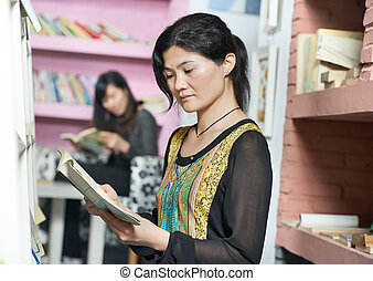 young chinese student girl with book in library - Chinese...