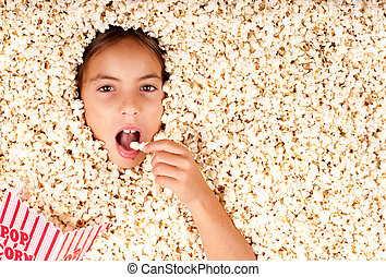 little girl buried in popcorn