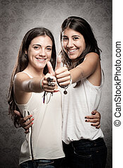 girls with thumbs up - two happy girls with thumbs up