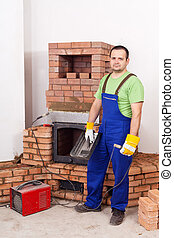 Worker mounting the door of a brick masonry heater