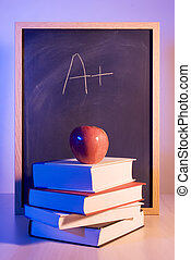 Education seriese - Apple on books in front of a chalkboard...