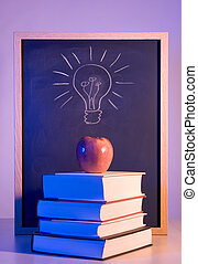 Bright idea - Apple on books in front of a chalkboard with a...