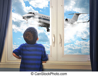 Boy Looking at Flying Airplane in Room - A young boy is...