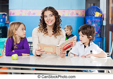 Teacher Holding Book With Children At Desk