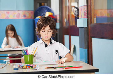 Boy With Color Pencils And Drawing Paper At Kindergarten