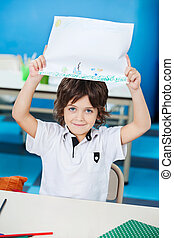 Boy Showing Drawing Paper In Classroom