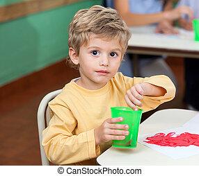 Little Boy Washing Paintbrush In Glass - Portrait of little...