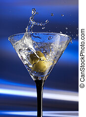 Olive splashing into a Martini photographed against a blue...