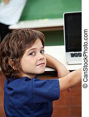 Boy With Laptop On Desk In Classroom - Portrait of cute boy...