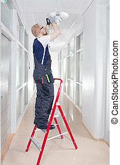 Janitor Fixing Broken Lamp - Janitor in Coverall Repairing...