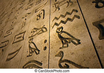 Hieroglyph. - Stone wall with ancient hieroglyphs engraved...