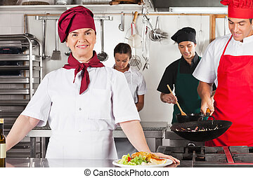 Confident Female Chef In Kitchen - Portrait of confident...