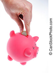 hand inserting coin to piggy bank on white background