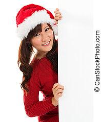 Christmas girl peeking from behind blank sign billboard.