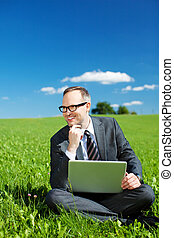 Man in meadow - Smiling businessman sitting on the...