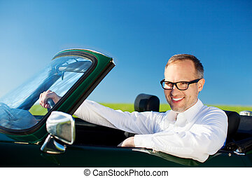 Happy man driving a convertible car over the blue sky...