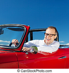 Happy man riding a red convertible car over the bright blue...