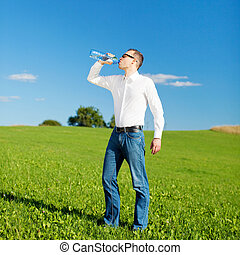 Man drinking bottled water in a field - Casual young man...