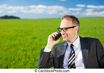 Businessman using his mobile in the countryside standing...