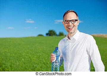 Smiling man drinking bottled water