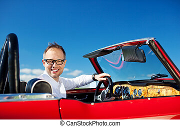 Man driving a vintage cabriolet with the hood down turning...