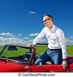 Young man standing in convertible car over the blue sky...