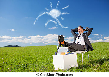 Break in meadow - Businessman sitting and resting feet on...