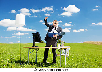 Young successful businessman raising his hands over the blue...