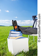 Relaxed businessman resting his feet on stack of books in...
