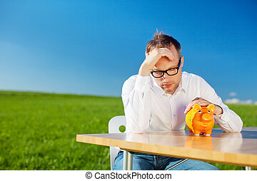 Dejected man looking at his piggy bank with his head in his...