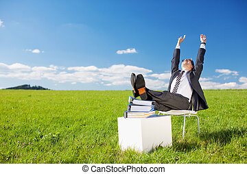 Businessman raising his arms with his feet on the stack of...
