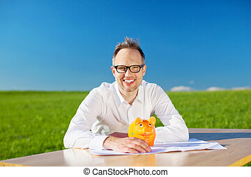 Happy businessman sitting with piggybank on his table...