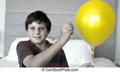 Boy piercing his balloon in the bedroom in selective color...
