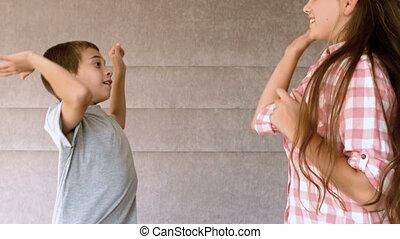 Siblings high-fiving in bedroom in slow-motion at 500 frames...
