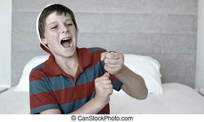 Happy boy using party popper in the bedroom in black and...