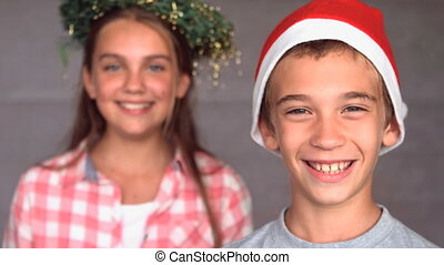 Smiling siblings with christmas hat in slow motion at 500...