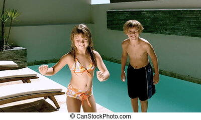 Young girl dancing while brother jumping in the swimming...