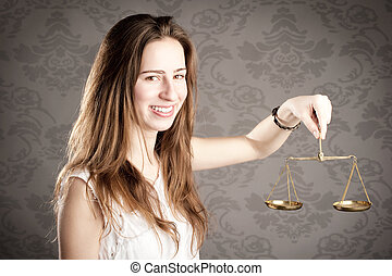 woman holding an hourglass - young woman holding a justice...