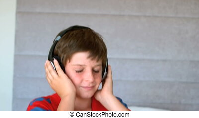 Dancing young boy enjoying music with headphones in slow...