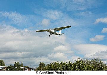 Small white airplane landing
