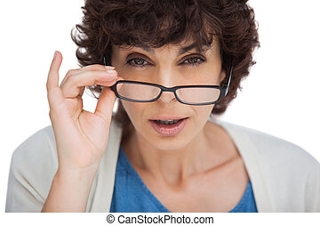 Portrait of a shocked woman looking over her glasses on...