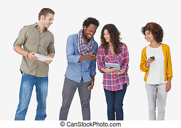 Four stylish friends looking at tablet and holding phones on...