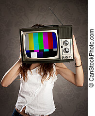 woman holding old television on her head - young woman with...