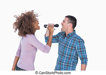 Fun duo singing to each other at karaoke on white background