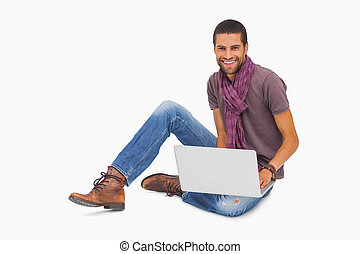 Happy man wearing scarf sitting on floor using laptop