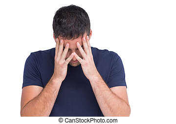 Sad man standing with his head in hands on white background