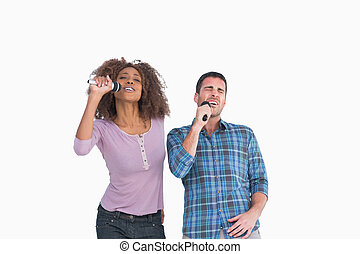 Fun pair singing at karaoke on white background