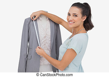 Fashion designer measuring blazer lapel on white background